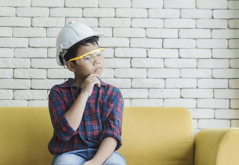 Little boy wearing a engineering helmet and looking throught window. royalty free stock images