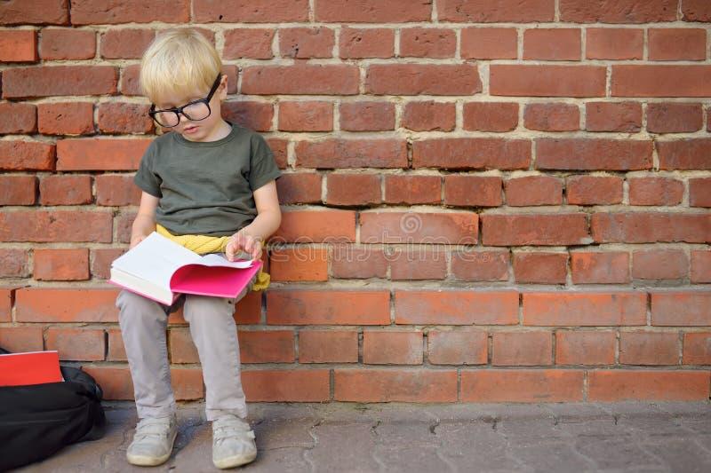Little boy wearing eyeglass doing homework on break near school building. Back to school concept royalty free stock images
