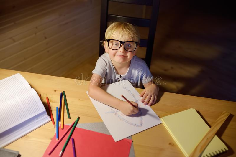 Little boy wearing glasses doing homework, painting and writing at home evening. Preschooler learn lessons - draw and color image royalty free stock photo