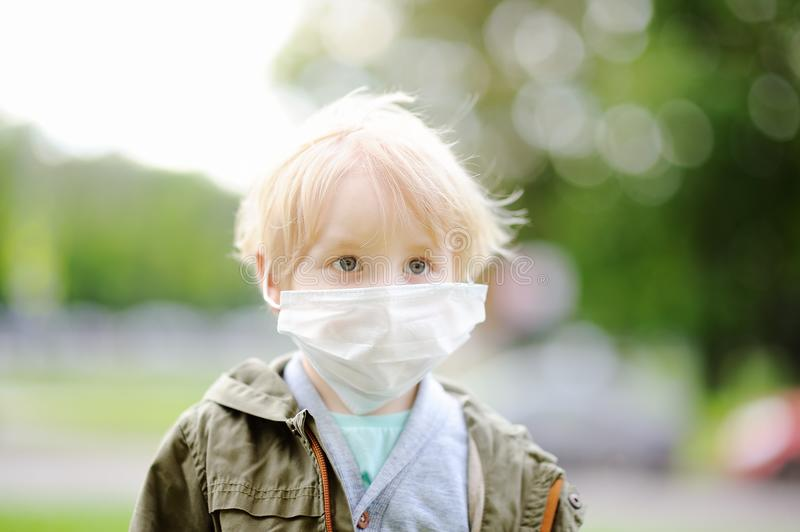 Little boy wearing medical face mask as protection against infectious diseases. Portrait of cute little boy wearing medical face mask as protection against royalty free stock photography