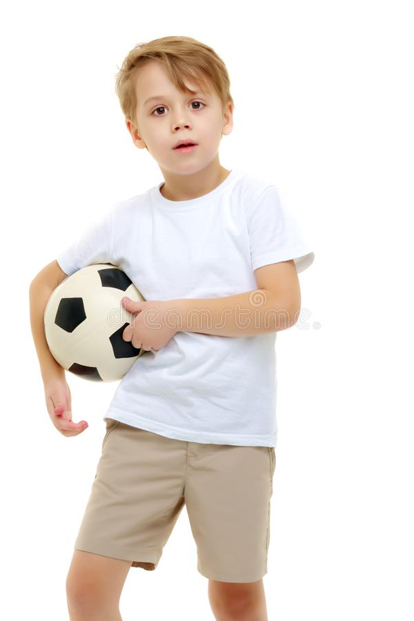 A little boy wearing a pure white t-shirt is playing with a socc stock photography