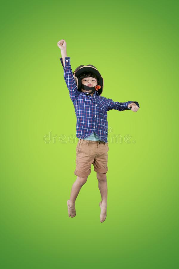 Little boy wears helmet during flying on studio. Portrait of little boy wearing a flight helmet while flying in the studio with green screen royalty free stock photos