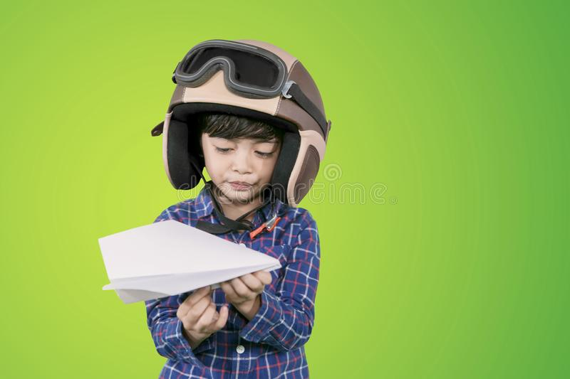 Little boy wears a helmet and hold paper plane. Picture of little boy wearing helmet while holding a paper plane and standing in the studio stock photo