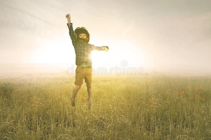 Little boy wears helmet during jumps in the meadow. Picture of a little boy wearing a flight helmet while jumping in the meadow with sunrise background stock photos