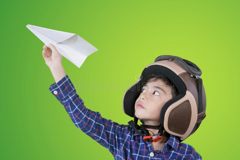 Little boy wears helmet during play a paper plane. Little boy wearing flight helmet while playing a paper plane in the studio with green screen background royalty free stock images