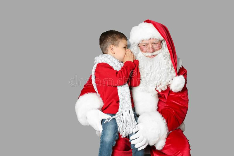 Little boy whispering in authentic Santa Claus` ear. On grey background royalty free stock photography