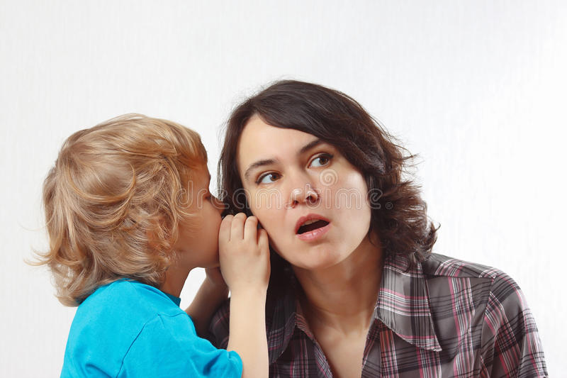 Little Boy Whispers To His Mother Something Into Her Ear Stock Image