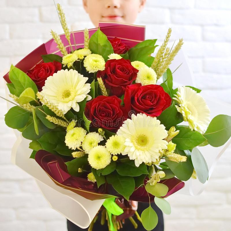 The little boy  with a beautiful bouquet of flowers for his mother. royalty free stock photos