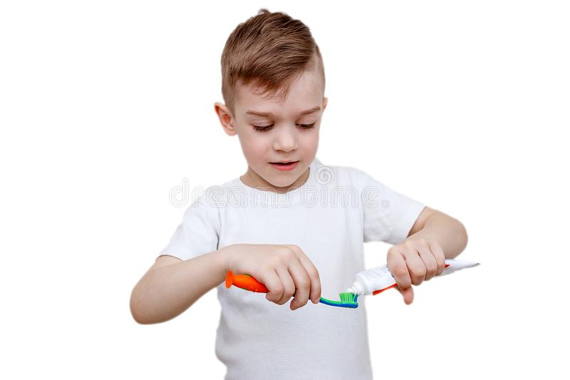 Little boy in white t-shirt squeezes toothpaste on brush. Health care, hygiene and childhood concept. Caries prevention. Little five-year-old boy in white t stock photography
