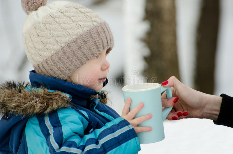 Little boy in winter clothes on a walk takes Mom mug of tea, close-up royalty free stock images