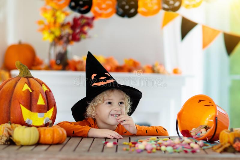 Kids in witch costume on Halloween trick or treat. Little boy in witch costume on Halloween trick or treat. Kids carving pumpkin lantern. Children celebrate royalty free stock photos