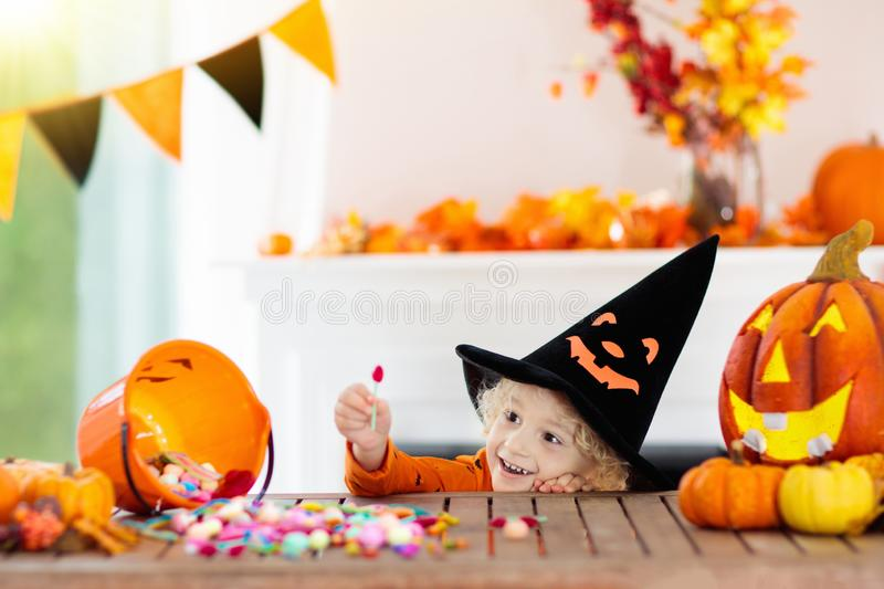 Kids in witch costume on Halloween trick or treat. Little boy in witch costume on Halloween trick or treat. Kids carving pumpkin lantern. Children celebrate stock image