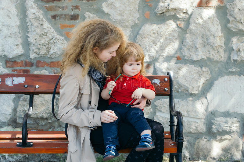 Little boy and woman on the bench royalty free stock photography