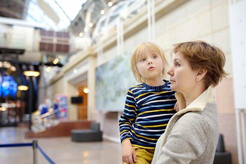 Little boy and woman looking an exposition in a scientific museum royalty free stock image