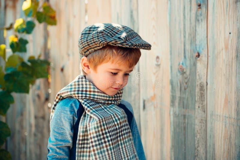 Little boy on a wooden wall background. Humble shy child. Melancholy. Romance. Melancholic mood. stock photography