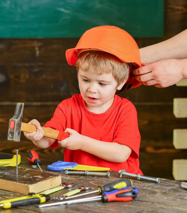 Little boy working with hammer. Daddy taking care of sons safety. Male hands holding orange protective helmet. Small kid stock photo