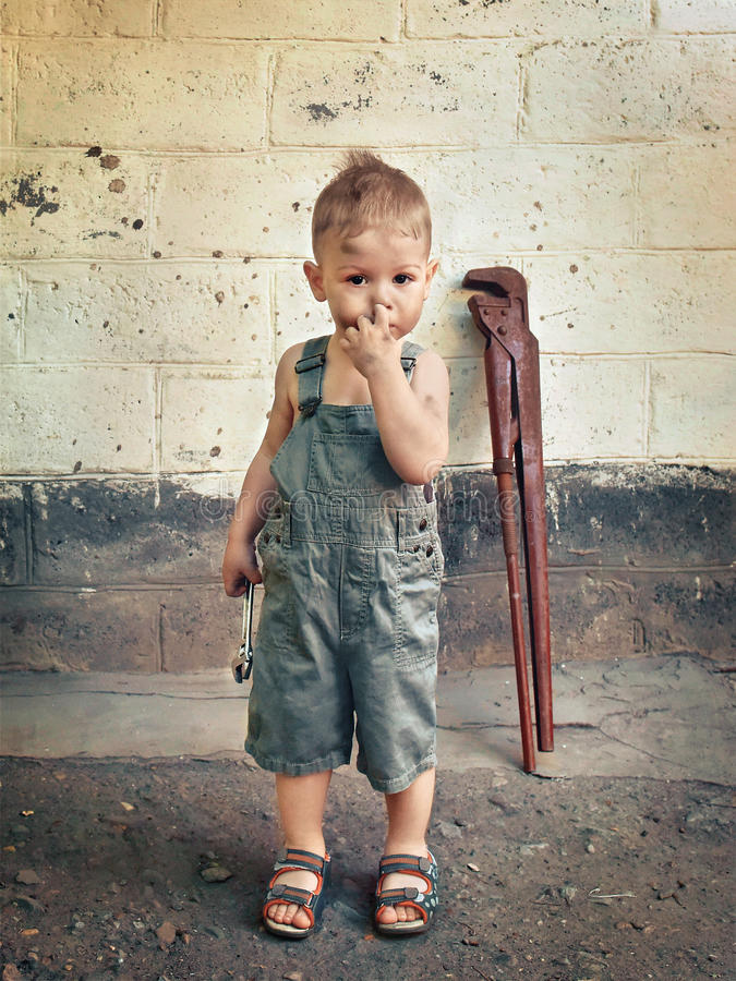 Little boy with a wrench standing at the wall stock photo