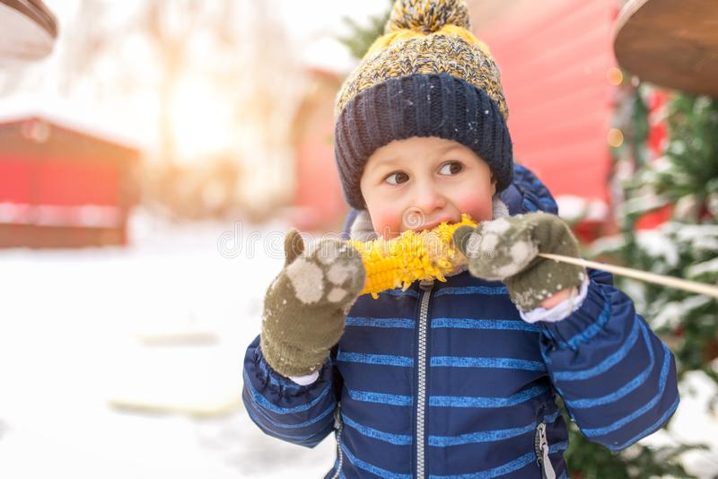 Little boy 2-3 years in a blue jacket and hat. The child in winter on the street eats boiled corn from a stick. Concept stock photos
