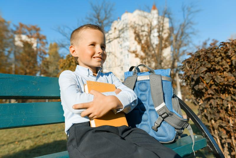 Little boy 6, 7 years old with a book. Portrait of a child with big book, reading and sitting on bench.  royalty free stock photos