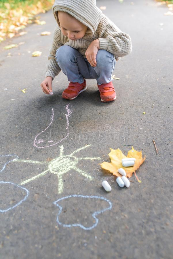 Little boy 3-5 years old, draws with colorful crayons on asphalt, in summer in fall in a city park. Warm clothes sweater royalty free stock photo