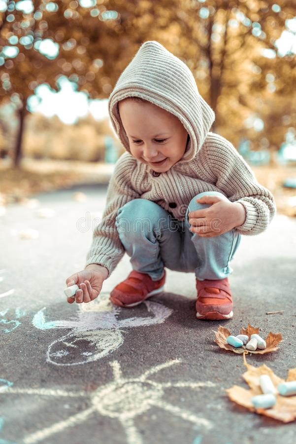 Little boy 3-5 years old, draws with colorful crayons pavement, laughs happy smiles rejoices, summer autumn city park. Little boy 4-5 years old, draws with royalty free stock image