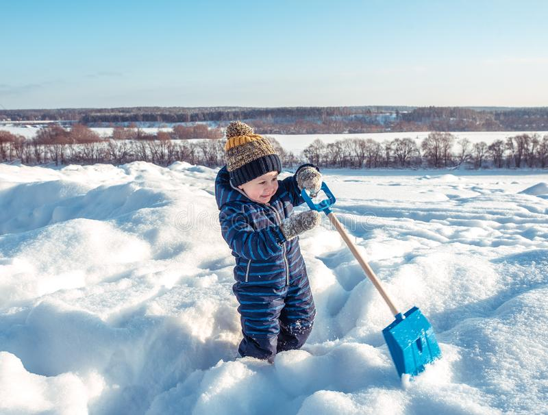 A little boy of 3 years old, in park in winter, plays with a shovel, digs snow. Happy cheerful bright sunny day. royalty free stock images