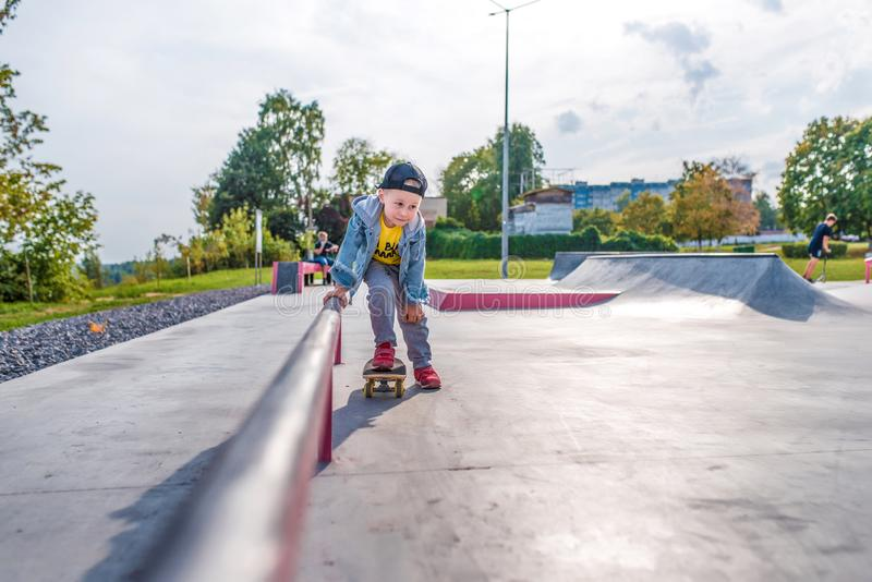 Little boy 3-5 years old, in summer on sports field in city, autumn on street, practicing skateboarding, casual wear royalty free stock photos
