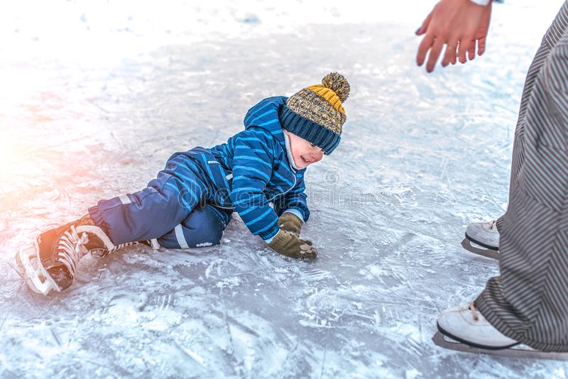 Little boy, 2-3 years old, winter uniform, blue overalls hat, fell on ice skates. The concept of first lesson skating stock photos