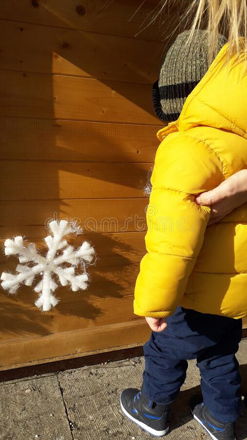 A little boy in yellow jacket look at the New year decoration with snowflake on wooden background. New year decoration with snowflake on wooden background. New stock photos