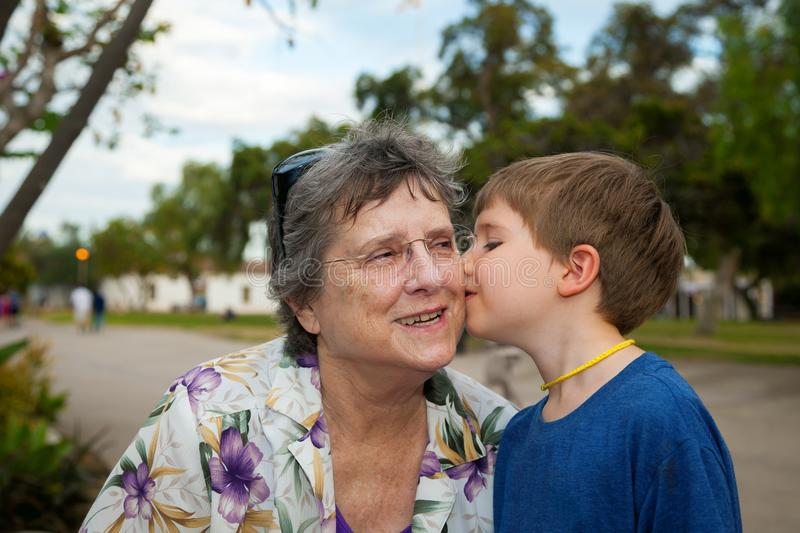 Little Boy With a Yellow Yarn Necklace Kisses His Grandmother on stock image