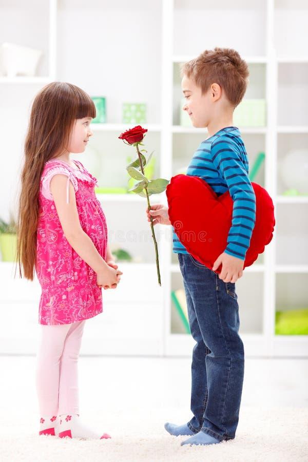 Little boyfriend giving flower royalty free stock images