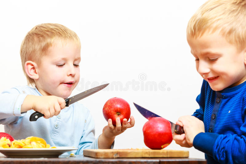Little boys cutting apple with a kitchen knife stock photography