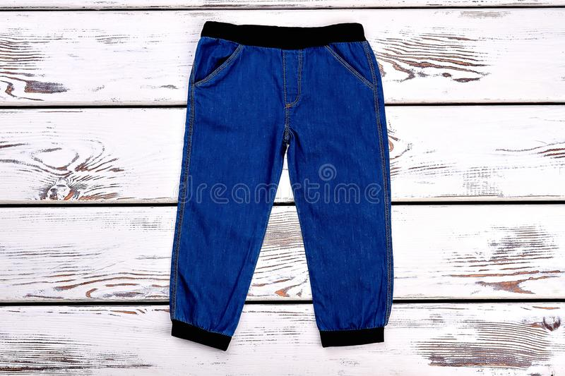 Little boys denim trousers. Baby boy new trendy sparing or autumn jeans on white wooden background, top view. Kids fashion apparel on sale stock photos