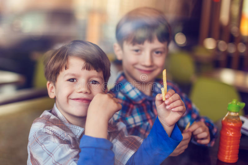 Little boys eating french fries in fast food restaurant royalty free stock images