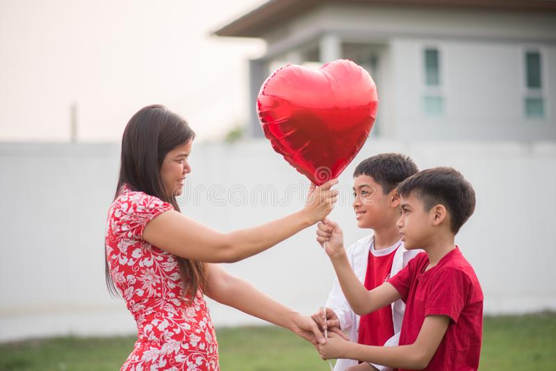 Little boys giving balloon heart to his mother love royalty free stock image