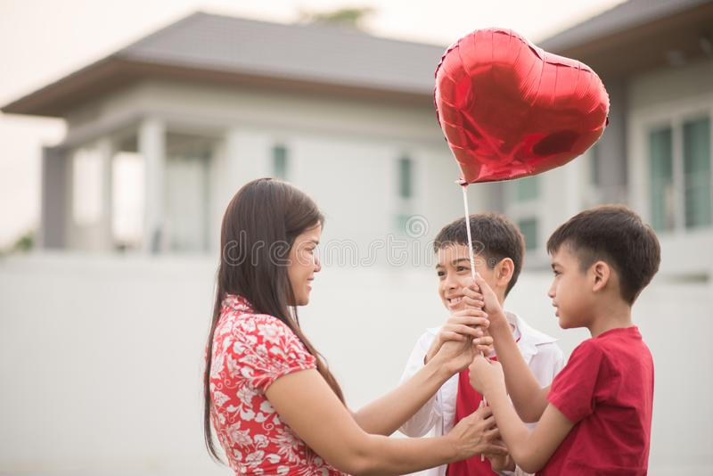 Little boys giving balloon heart to his mother love stock photo