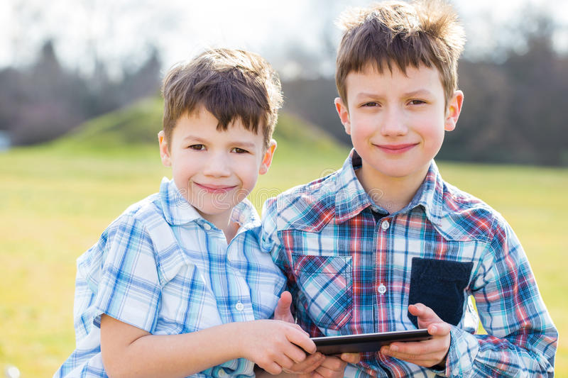 Little boys holding tablet outdoor royalty free stock photos