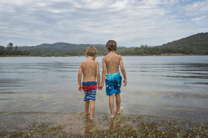 Little boys at mountain lake royalty free stock photos