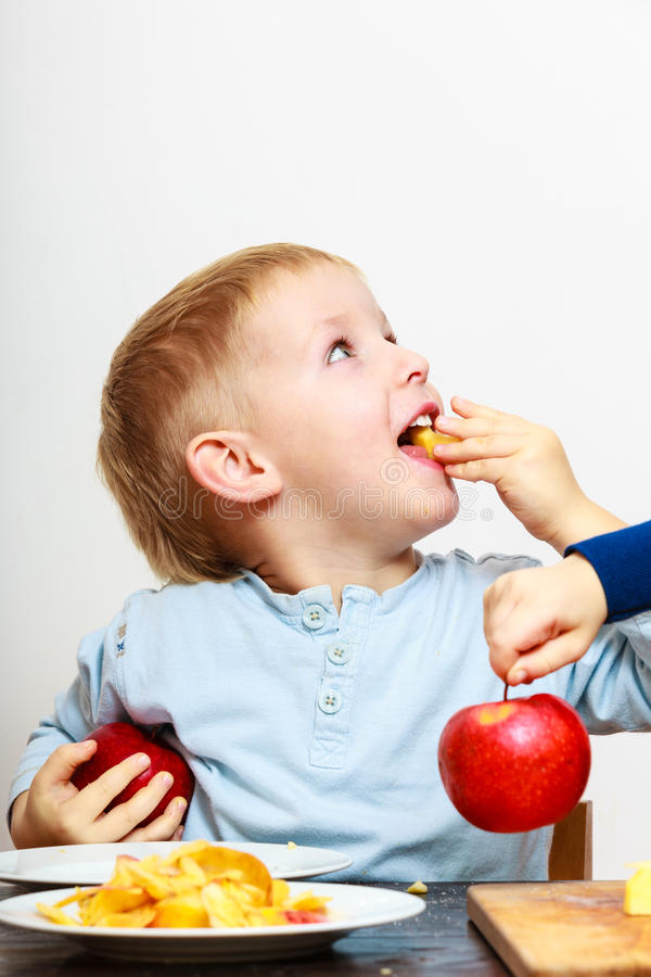 Little boys peeling apple cooking at home. royalty free stock images