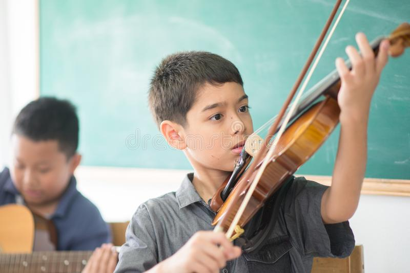 Little boys play and practice violin in the music class. Room royalty free stock photography