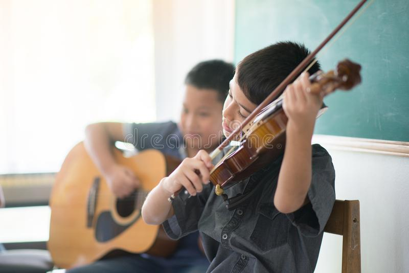 Little boys play and practice violin in music class room. Little boys play and practice violin in the music class room stock photography