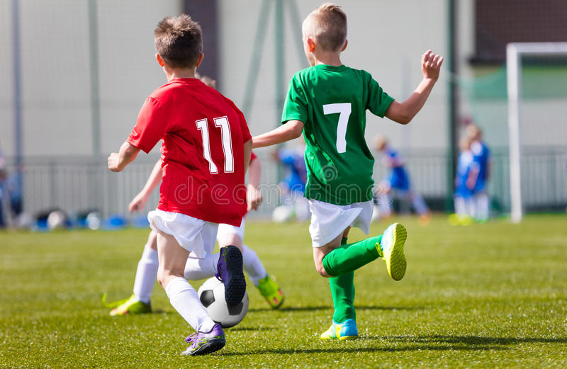 Little boys playing football soccer game on sports field stock photography