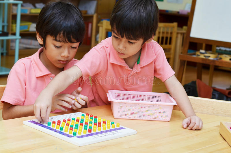 Little boys study color of pin made of montessori educational ma stock images