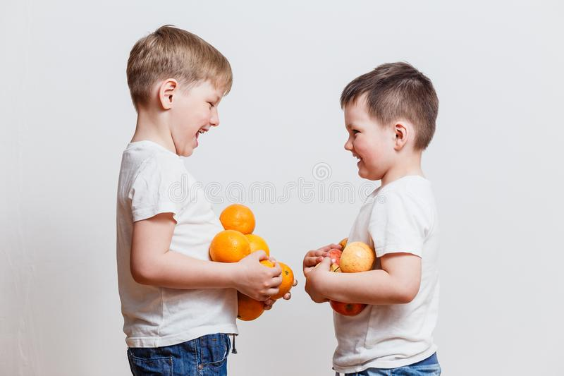 Little boys in white t-shirts with fruit in hand royalty free stock photo