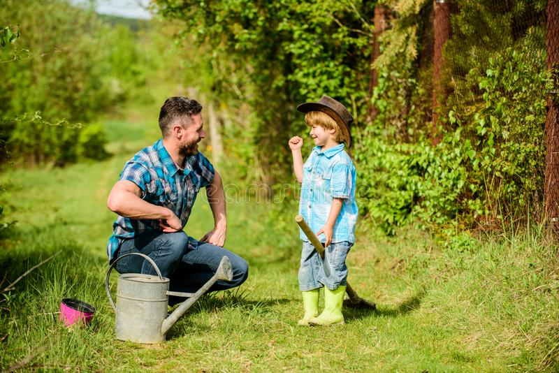 Little break. happy earth day. Family tree nursering. father and son in cowboy hat on ranch. watering can, pot and. Shovel. Garden equipment. Eco farm. small stock photo