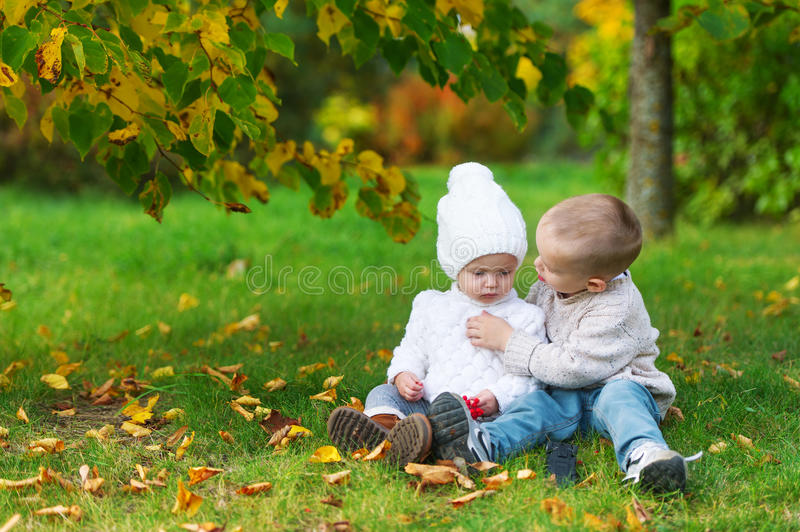 The little brother cares for the baby sister in the autumn park. The little brother cares for the baby sister in the autumn city park stock photos