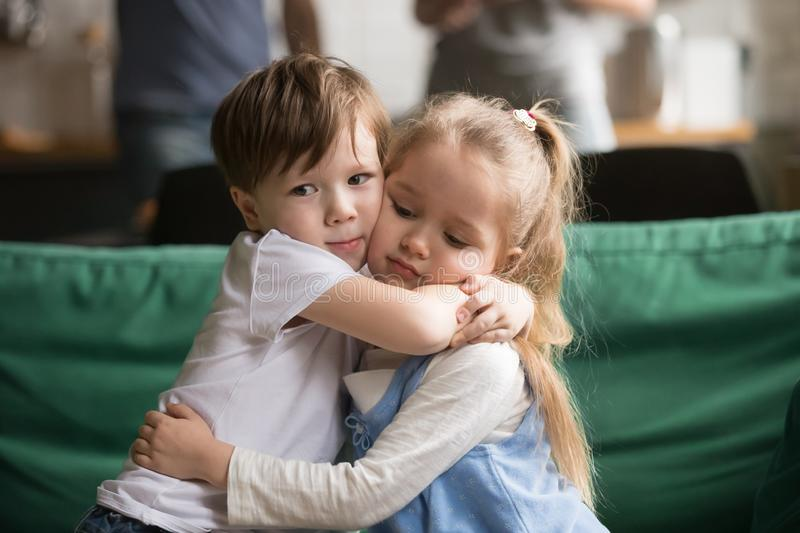Little brother hugging upset sister sitting on couch royalty free stock photography