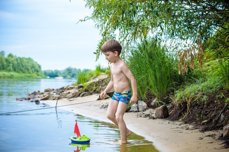 Little brother playing with paper boats by a river on warm and sunny summer day. Little sibling brother playing with paper boats in a river or lake on warm and royalty free stock images