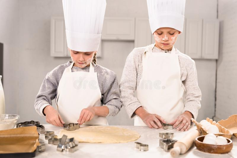 Little brother and sister in chef hats and aprons cutting out dough for cookies at table. In kitchen stock photo