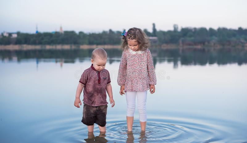 Little brother and the sister have fun near the river. Happy childhood stock photo